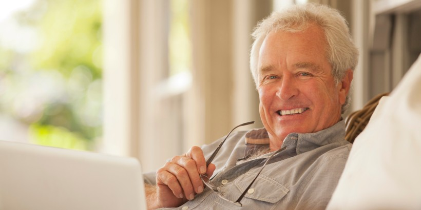 Portrait of smiling senior man using laptop on porch